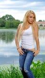 Junge blonde Frau im weißen Trägershirt und in den Jeans Lizenzfreie Stockfotos