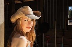 Junge blonde Frau im Westhut-heraus Tür-Porträt Stockfotos