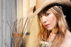 Junge blonde Frau im Westhut-heraus Tür-Porträt Stockbild