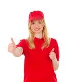 Junge blonde Frau kleidete den Händler mit roten Uniformen o.k. sagend Lizenzfreie Stockfotografie