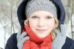 Junge blonde Frau mit Beanie- und Schalwinterholzporträt Stockfotografie