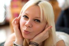 Junge blonde Frau luft-küsst Lizenzfreie Stockfotografie