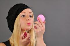 Junge blonde Frau malt Lippen auf grauem Hintergrund. Stockbilder