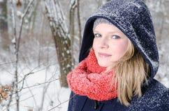 Junge blonde Frau mit Beanie- und Schalwinterholzporträt Stockfoto
