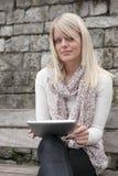 Junge blonde Frau mit blauen Augen mit Tablette Lizenzfreies Stockbild