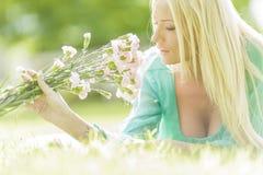 Junge blonde Frau mit Blumen Lizenzfreie Stockbilder