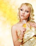 Junge blonde Frau mit Champagnerglas Stockbild