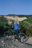 Junge blonde Frau mit dem Fahrrad und an dem genießen Leben die Hintergrundberge Stockfotos