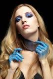 Junge blonde Frau mit dem langen Haar und den Händen gemalt im blauen pai Lizenzfreies Stockbild