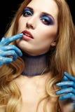 Junge blonde Frau mit dem langen Haar und den Händen gemalt im blauen pai Stockbild
