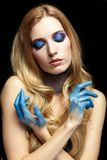 Junge blonde Frau mit dem langen Haar und den Händen gemalt im blauen pai Lizenzfreie Stockfotos