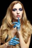 Junge blonde Frau mit dem langen Haar und den Händen gemalt im blauen pai Lizenzfreies Stockfoto