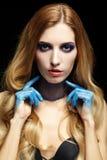 Junge blonde Frau mit dem langen Haar und den Händen gemalt im blauen pai Stockfotografie