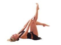 Junge blonde Frau mit den Fahrwerkbeinen in einer Luft Stockfoto