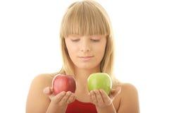 Junge blonde Frau mit den roten und grünen Äpfeln Lizenzfreie Stockfotos