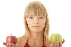 Junge blonde Frau mit den roten und grünen Äpfeln Lizenzfreie Stockbilder