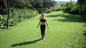 Junge blonde Frau mit den Zöpfen, die Hampelmanneignungs-Übungstraining auf der Wiese im grünen Sommerpark tun langsam stock video footage