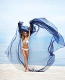 Junge blonde Frau mit der blauen Seide, die auf dem Strand aufwirft Stockfotos