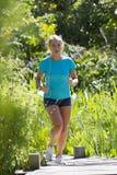 Junge blonde Frau mit der Musik, die in grünen natürlichen Hintergrund läuft Lizenzfreies Stockbild