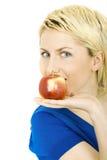 Junge blonde Frau mit einem Apfel Stockfotografie