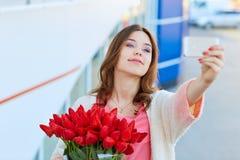 Junge blonde Frau mit einem Blumenstrauß von roten Tulpen nimmt selfie Lizenzfreies Stockfoto