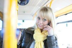 Junge blonde Frau mit einem Intelligenttelefon innerhalb eines Busses Lizenzfreie Stockbilder