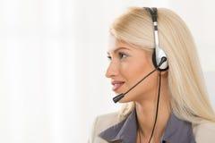 Junge blonde Frau mit einem Kopfhörer Stockbild