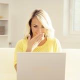 Junge blonde Frau mit einem Laptop Stockfotografie