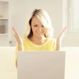 Junge blonde Frau mit einem Laptop Lizenzfreie Stockfotos