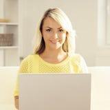 Junge blonde Frau mit einem Laptop Stockbild