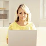 Junge blonde Frau mit einem Laptop Stockfoto