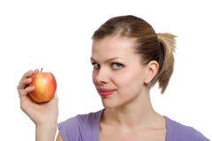 Junge blonde Frau mit einem roten Apfel Lizenzfreie Stockfotos