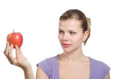 Junge blonde Frau mit einem roten Apfel Stockfoto