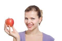 Junge blonde Frau mit einem roten Apfel Stockfotos