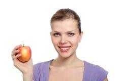 Junge blonde Frau mit einem roten Apfel Stockbilder