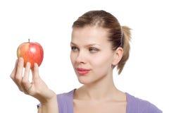 Junge blonde Frau mit einem roten Apfel Stockfotografie