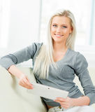 Junge blonde Frau mit einem Tablet-Computer Stockfotografie