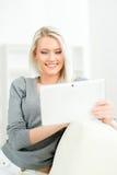 Junge blonde Frau mit einer Tablette Stockbild