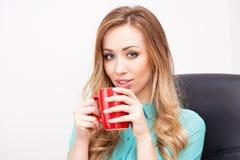 Junge blonde Frau mit einer Tasse Tee Lizenzfreies Stockfoto