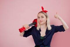 Junge blonde Frau mit einer Ukulele auf Schulter Zeigt sich eine Fingergeste Es ` s groß stockfotografie