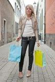 Junge blonde Frau mit Einkaufenbeuteln Stockbild