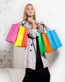 Junge blonde Frau mit Einkaufenbeuteln Stockfotos