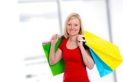 Junge blonde Frau mit Einkaufenbeuteln Lizenzfreie Stockbilder