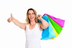 Junge blonde Frau mit Einkaufstaschen und dem Daumen oben Lizenzfreie Stockbilder