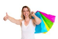 Junge blonde Frau mit Einkaufstaschen und dem Daumen oben Stockbild