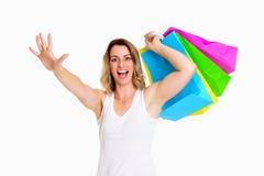 Junge blonde Frau mit Einkaufstaschen und der Hand oben Stockfotografie