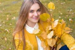 Junge blonde Frau mit Gelb verlässt im Park Lizenzfreie Stockfotos