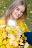 Junge blonde Frau mit Gelb verlässt im Park Lizenzfreie Stockbilder