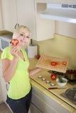 Junge blonde Frau mit Gemüse auf Küche Stockbilder