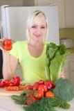 Junge blonde Frau mit Gemüse auf Küche Lizenzfreie Stockfotografie